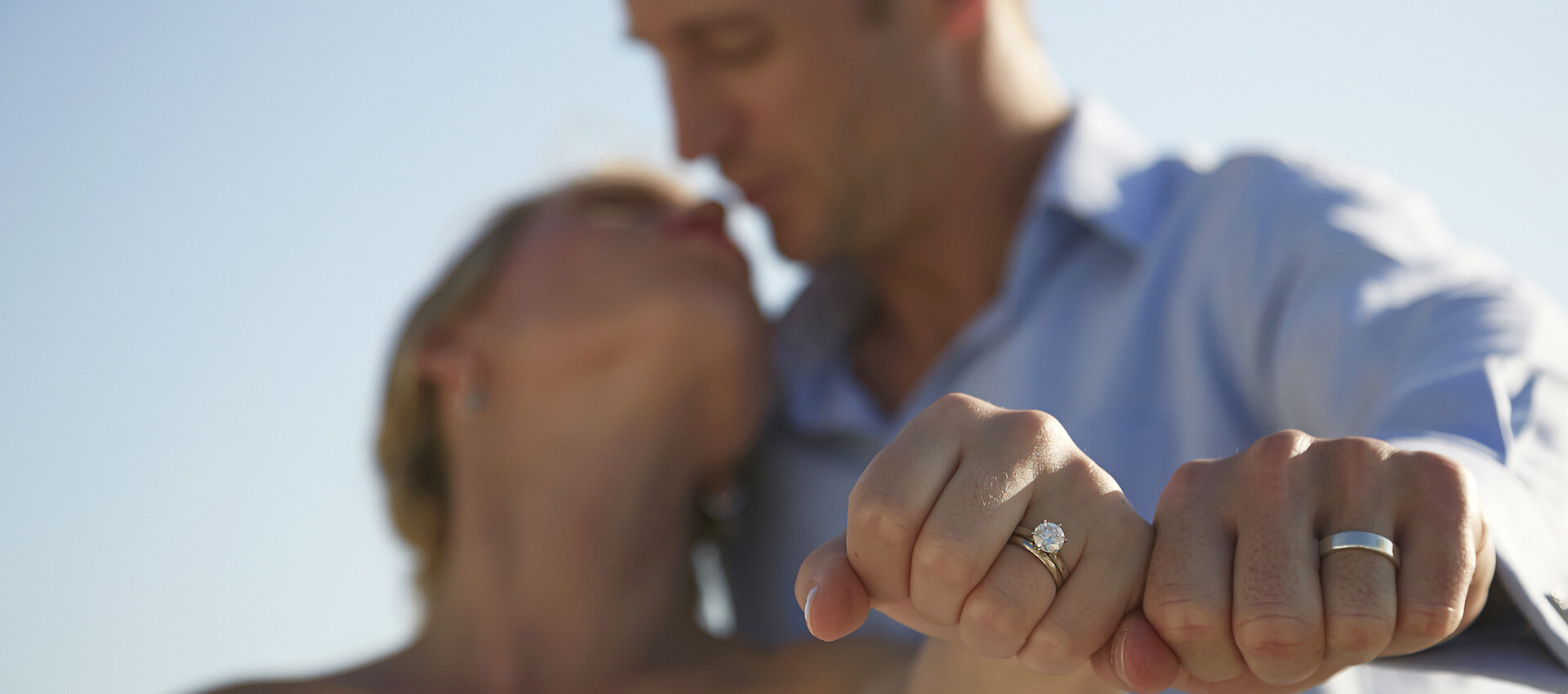 A bride and groom showing their rings while kissing.